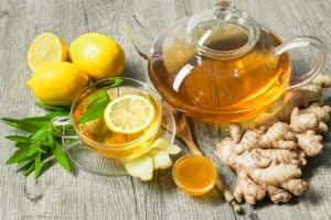 Ginger tea with lemon and honey on wooden table.