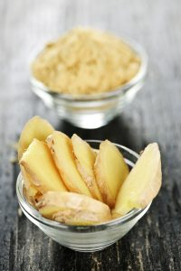 Sliced and ground ginger in glass bowls.