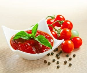 Red tomato sauce in a white bowl.